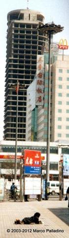 Mendicante nelle vie di Pechino davanti ai nuovi fastfood McDonald