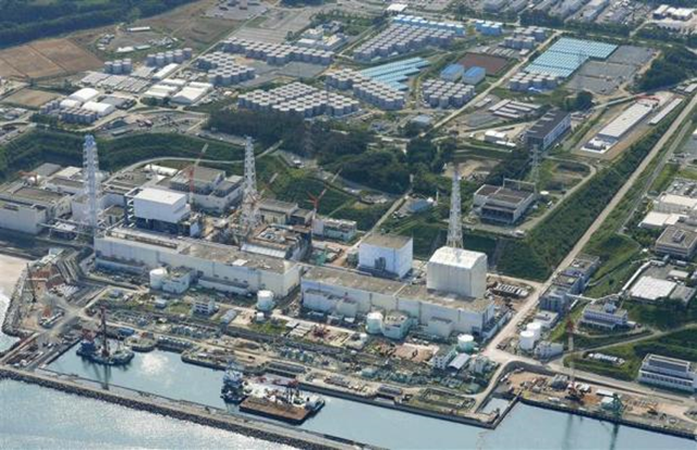 An aerial view shows the Tokyo Electric Power Co.'s (TEPCO) tsunami-crippled Fukushima Daiichi nuclear power plant and its contaminated water storage tanks (top) in Fukushima, in this photo taken by Kyodo on 31 August 2013. Storage tanks at the Fukushima nuclear plant like one that spilled almost 80,000 gallons of radioactive water in 2013 were built in part by workers illegally hired in one of the poorest corners of Japan, say labor regulators and some of those involved in the work. Photo: Reuters / Kyodo