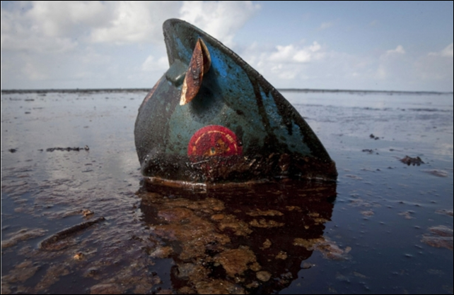 A hard hat from an oil worker lies in oil from the Deepwater Horizon spill on East Grand Terre Island, Louisiana. Photo: Lee Celano / Reuters