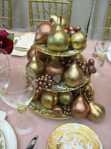 Plastic fruit that we tied into our pink and gold color palette serves as a stylish and inexpensive centerpiece.