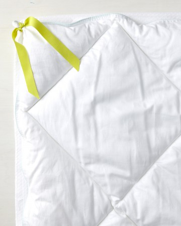 Keep your duvet and your comforter in place by turning the cover inside out and sewing two pieces of five-inch-long fabric tape to all four corners. Then tie the fabric tape around each corner of the comforter.