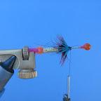 Piórem badger wykonujemy jeżynkę typu pallmer, ale tylko na czarnej części tułowia. Wzmacniamy ją przeciwskrętnymi nawojami drutu. Po tej operacji wyczesujemy dubbing tak, aby jego włókna wymieszały się z promieniami jeżynki. Następnie tuż za pierwszą jeżynką wykonujemy drugą, tym razem z błękitnego piórka.