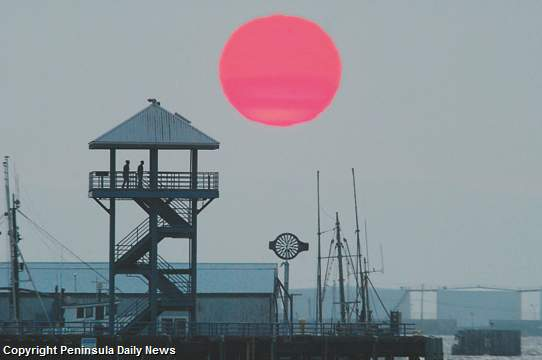 The sun sets behind Port Angeles City Pier Monday night, 9 July 2012. Smoke from wildfires in Siberia is producing spectacular sunsets. Keith Thorpe / Peninsula Daily News