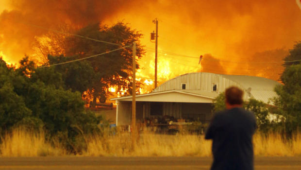 Dean Smith watches as the Yarnell Hill Fire encroaches on his home in Glenn Ilah on 30 June 2013 near Yarnell, Arizona. / David Kadlubowski/ AP