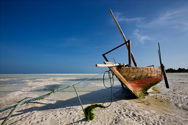 'Ephemeral Drought' by InasiaJones. Along the East Coast of Zanzibar at low tide, one can walk a long distance before touching the waves that seem kilometers away. Women of nearby villages come to collect seaweed and fishermen are returning home with their daily catch, while their boats seem out of place. Photo: InasiaJones / Trek Earth