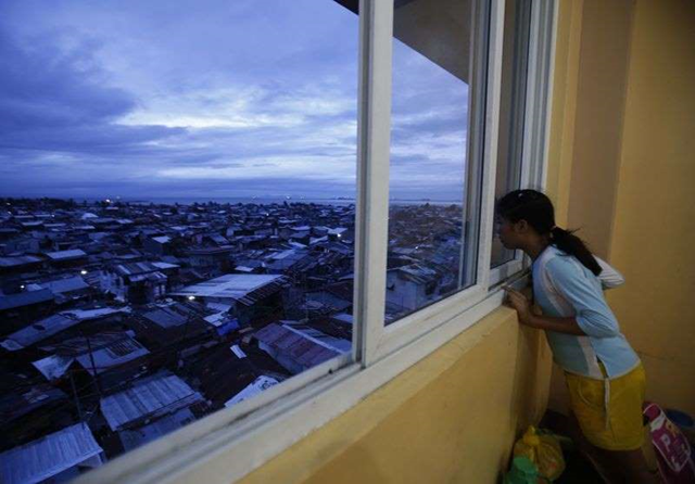 A girl looks out of a window as rain clouds cover the sky, at an evacuation centre for the coastal community, to shelter from typhoon Hagupit, in Manila, 8 December 2014. Photo: Cheryl Gagalac / REUTERS