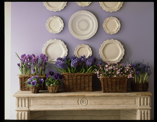 Spring bulbs tucked inside baskets on this mantle arrangement create a beautiful spring landscape.