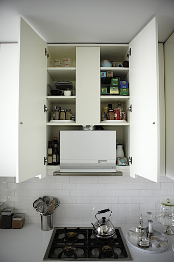 The cabinet above the cook top houses a fan and vent that creates small cubbies perfect for storing cooking oils, spices, wraps, storage bags and other small kitchen tools.