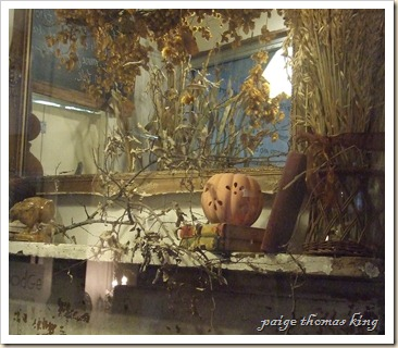 mantel with wheat, branches, bookd and pierced pumpkin