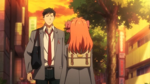 Nozaki stands facing Chiyo, our view over her shoulder, in the orange glow of evening
