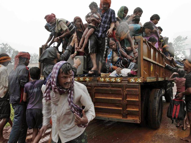 Evacuated Indian villagers get down from a truck at a relief camp as it rains near Berhampur, India, on 12 October 2013. Hundreds of thousands of people living along India's eastern coastline were taking shelter Saturday from a massive, powerful cyclone, dubbed Phailin, that was set to reach land packing destructive winds and heavy rains. Photo: Bikas Das / AP