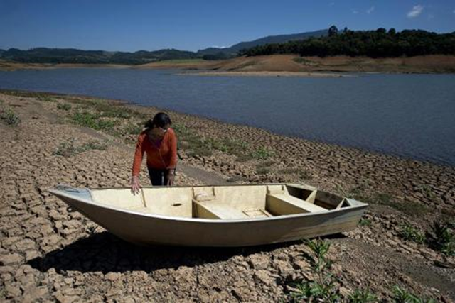 A local resident stands next to a boat near the bank of Jacarei river dam, in Piracaia, as a record drought affects Sao Paulo state in Brazil, on 19 November 2014. Photo: Nelson Almeida