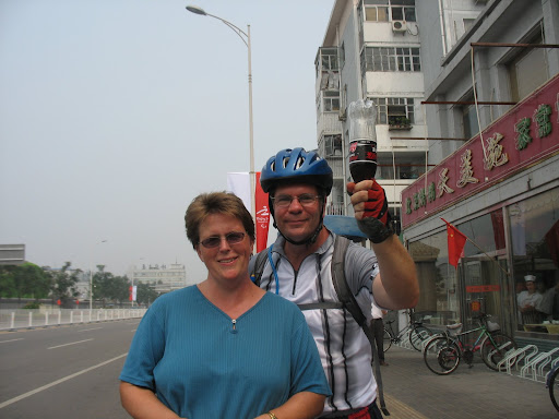 Catherine and Mark, being silly in Beijing, holding a bottle of Diet Coke, upside down, like an Olympic torch.