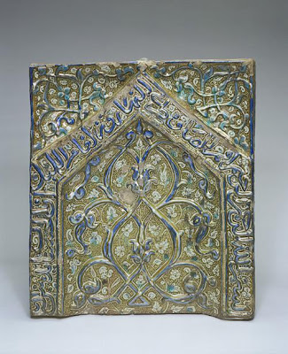 Panel from a mihrab | Origin:  Probably Kashan,  Iran | Period: early 14th century  Il-Khanid period | Details:  This glazed panel, adorned with an arabesque design in relief, originally formed the upper section of large tile mihrab . It is inscribed with a verse from the Koran (sura 11, verse 114): In the name of God, the Merciful, the Compassionate.  Perform prayer morning and evening, and in the watches  of the night. Behold, good works and drive away evil. | Type: Molded stone-paste; painted under glaze with color and over glaze with luster | Size: H: 66.4  W: 59.0   D: 10.7  cm | Museum Code: F1909.319 | Photograph and description taken from Freer and the Sackler (Smithsonian) Museums.