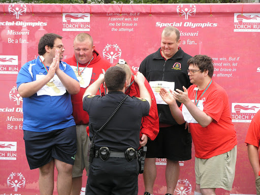 A member of the Springfield Police Department presenting medals to Special Olympics athletes. (Photo credit: Jeremy Shreckhise)