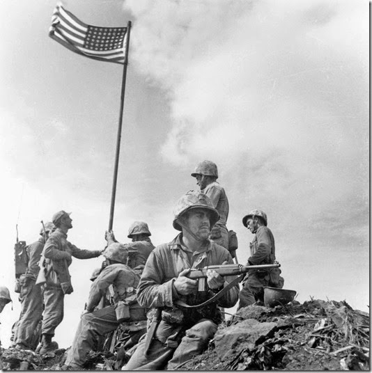 This is the first flag raising on the top of Mt. Suribachi. The famous flag-raising photo was taken when the second flag was put up later that day. This photo was taken by Leatherneck's Lou Lowery.