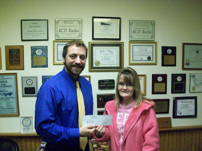 Winner of the Christmas Cash Call Felicia Humphries receives her check for $1,000 from KCII General Manager Joe Nichols