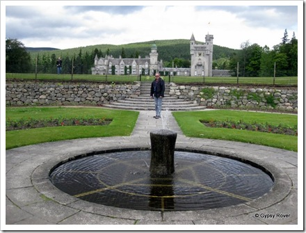 Balmoral Castle viewed from the grounds. The fountain is an old mooring bollard from Aberdeen.