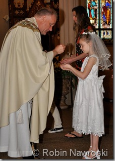 Fr. Timothy Yanta and #5 of 5 during the Wednesday Mass following her First Communion - photo courtesy of Robin Nawrocki Photography