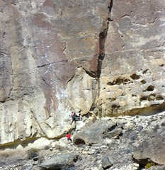 The guy in red is belaying the climber above.