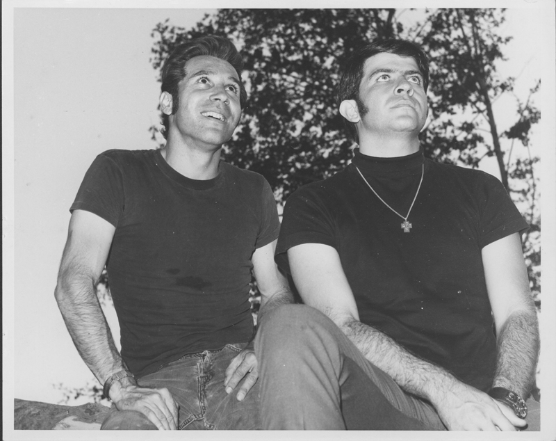 Pat Rocco and Reverend Troy Perry sitting outside. Circa 1970.
