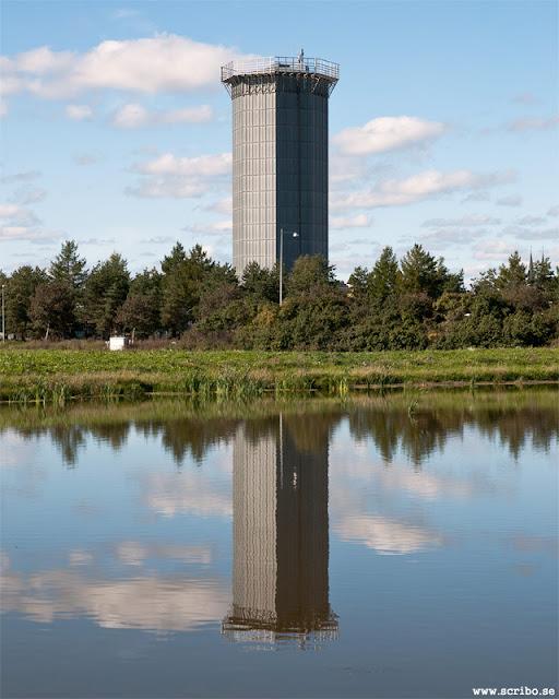 Kylvattentornet vid Uppsala reningsverk speglar sig i dagvattendammen.