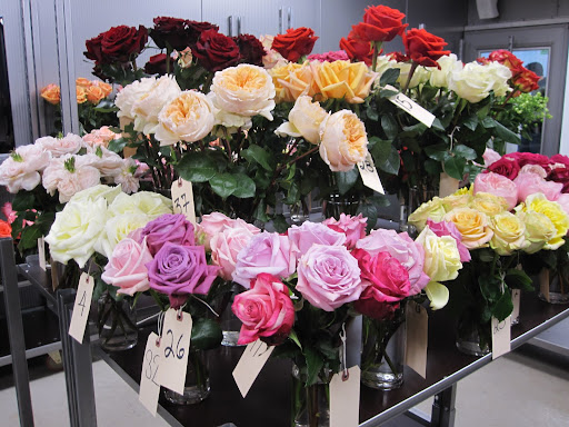 On a table at he back of the shop is a display of roses that are not available yet at the store.