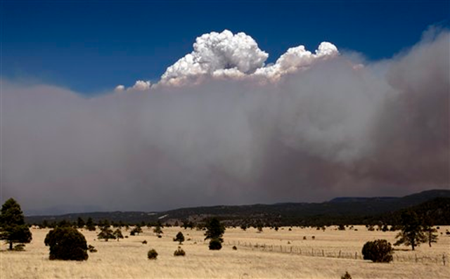 A smoke plume over the east side of the Wallow Fire climbs high into the sky Monday afternoon, June 6, 2011, as strong winds fanned the Wallow Fire in Eager, Ariz. AP Photo / The Arizona Republic, Pat Shannahan