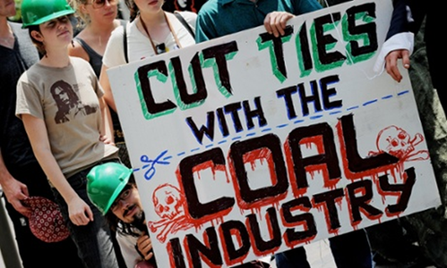Enviroment activists display an anti-coal industry placard outside the New South Wales Parliament building in Sydney. Photo: Greg Wodd / AFP / Getty
