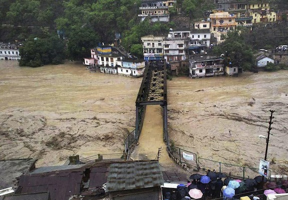 People gather to watch a bridge submerged in the flooded water of the River Ganges in Rudraprayag, in northern Indian state of Uttarakhand, India, Tuesday, 18 June 2013. Photo: AP