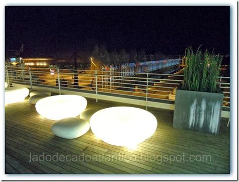 Imagem do 3º andar do Centro Comercial Vasco da Gama, Parque das Nações, Lisboa. Iluminadas lá embaixo em direção ao rio Tejo, estão bandeiras de todos os países , ladeadas por um espelho d'água.