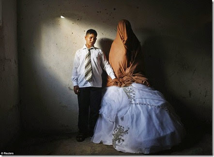 Palestinian groom Ahmed Soboh, 15 and his bride Tala, 14, stand inside Tala's house during their wedding party in the town of Beit Lahiya, near the border between Israeli and Gaza Strip September  - Copy