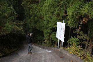 横沢川第2ダムへの通路入口にある放流注意看板を撮影する宮島さん