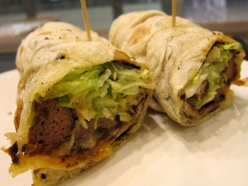 Lamb Sheik Kebab Wrap: Minced grilled kebab, lettuce, onions, tomato, and yoghurt wrapped in soft naan