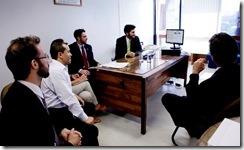 Foto do sorteio - pessoas em torno de uma mesa observando uma tela de computador