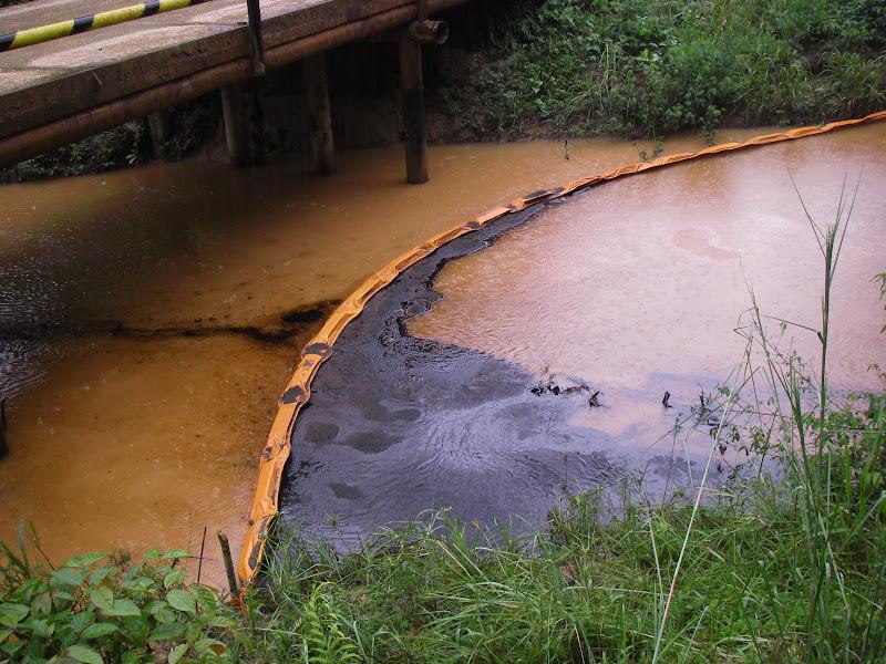 An oil spill flows down Chuuntsa Creek in Oil Block 1-AB