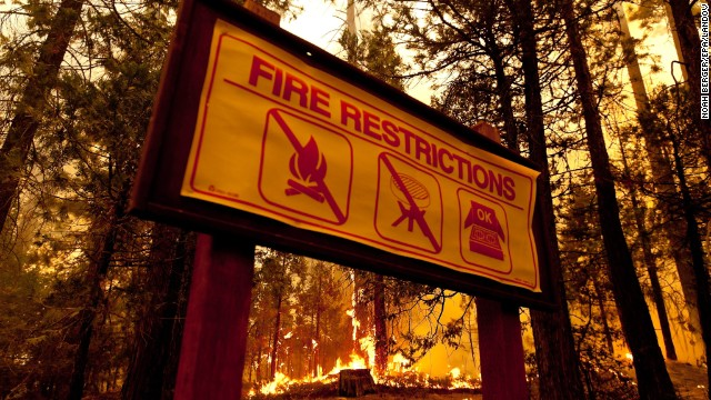 A forest fire approaches the border of Yosemite National Park on 23 August 2013. A sign reads 'Fire Restrictions'. Photo: Noah Berger / EPA / Landov