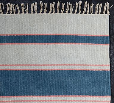 The thin salmon stripes intensify the blue on this beautiful rug. (potterybarn.com)