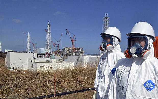 TEPCO workers stand near the crippled Fukushima Daiichi nuclear power plant reactor buildings in Fukushima, 29 February 2012.  Yoshikazu Tsuno / REUTERS via telegraph.co.uk
