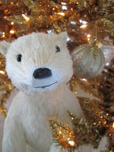 A polar bear peaking through the Christmas Trees.