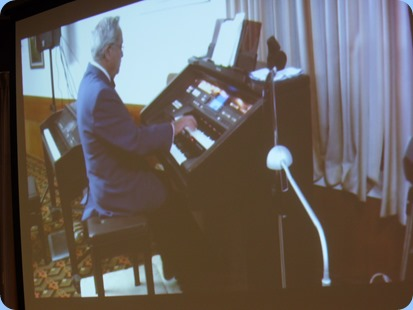 Our Special Guest Artist, Ron Clark, playing the Club's Technics GA3 organ. Ron chose themes for each of his segments which was most enjoyable. Seen here with a shot from the big screen.