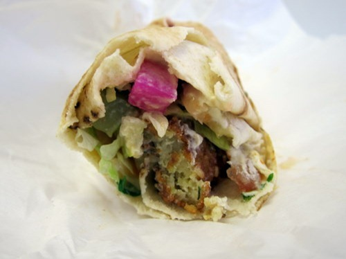 Classic Falafel Wrap served in Arabic style Lebanese bread with Fresh Tomatoes, Fresh Lettuce, Freshly Chopped Parsley, Hommous, and Fried Aubergines, topped with Special Tahina Sauce (Sesame Paste and Lemo