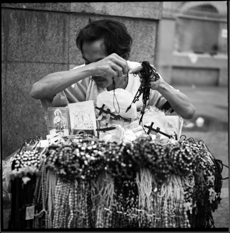 A street vendor wipes sweat off his forehead while selling rosaries and other religious items outside the church in Quiapo, Manila on a hot afternoon.