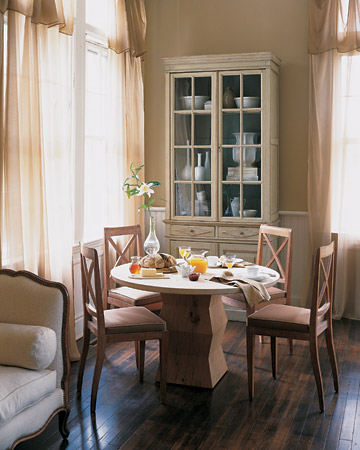 In this very Parisian breakfast room, there is as much cream as there is coffee: An eggshell-colored cupboard, curtains of pale chiffon, light woods, tan piping on the seat cushions, and snowy wainscoting all help to enrich the cafe au lait brown of the walls.