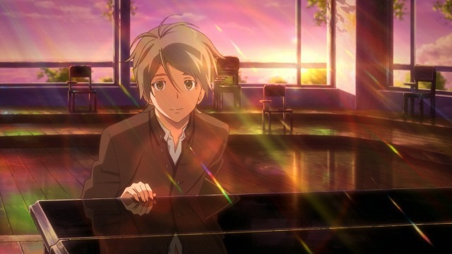 Ryouichi looks up, smiling, from a grand piano