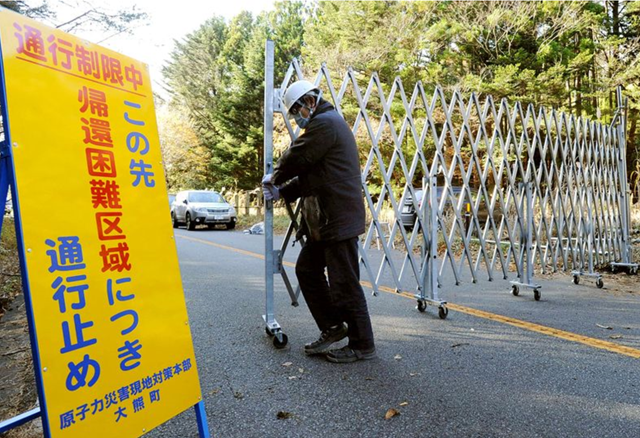 An official closes a barrier at an access point to the 'Difficult-to-return zone' in Okuma, Fukushima Prefecture. Photo: Asahi Shimbun