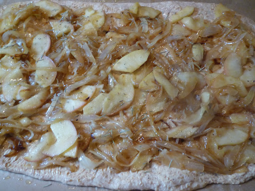 Top the pizza crust with the onion-apple mixture and add a little rosemary.
