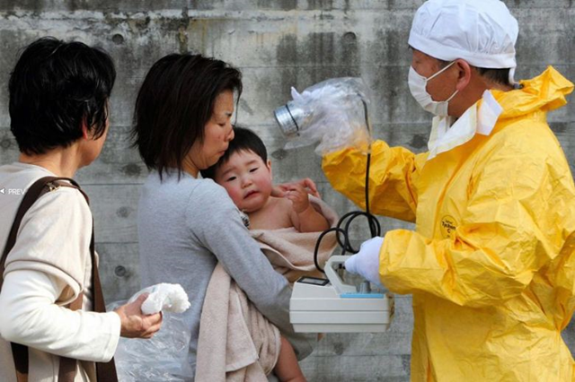 A worker checks a mother and baby for radiation near Fukushima, Japan, 14 March 2011.