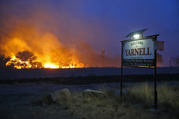 A wildfire burns homes in Yarnell, Arizona on Sunday, 30 June 2013. An Arizona fire chief says the wildfire that killed 19 members of his crew near the town was moving fast and fueled by hot, dry conditions. The fire started with a lightning strike on Friday and spread to 2,000 acres on Sunday amid triple-digit temperatures. Photo: David Kadlubowski / The Arizona Republic / AP