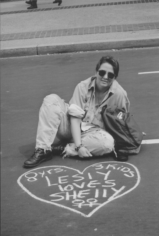 "Lesbian sits before a chalk drawing of a heart with the text ""8 yrs. 3 kids Lesly loves Shelly"" at the March on Washington. 1993."